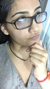 Sargam posing as if she's thinking very profoundly with her thick black framed glasses on