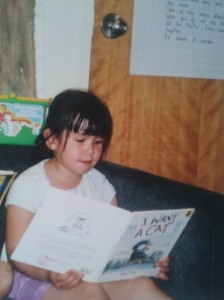 "Old Photograph of Liana from Kindergarten reading a book titled ""I Want a Cat"""