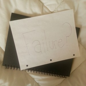 "A black notebook with a piece of lined paper on top of it that has ""Failure?"" written on it"