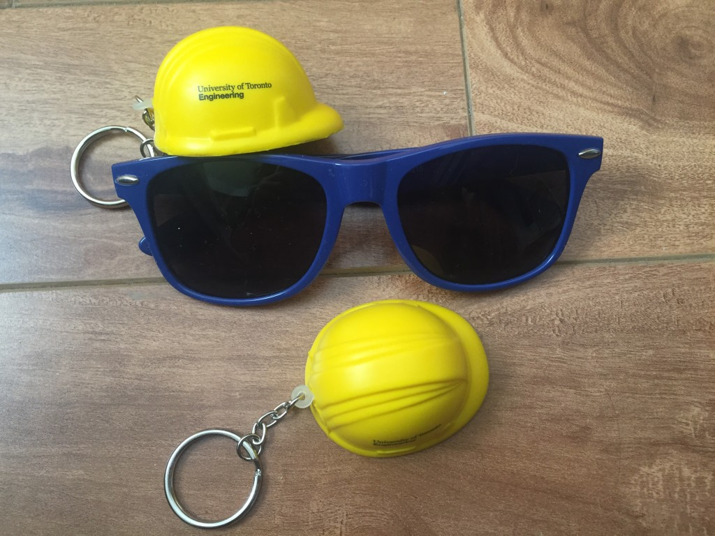 Two yellow keychains of hard hats, a pair of blue sunglasses