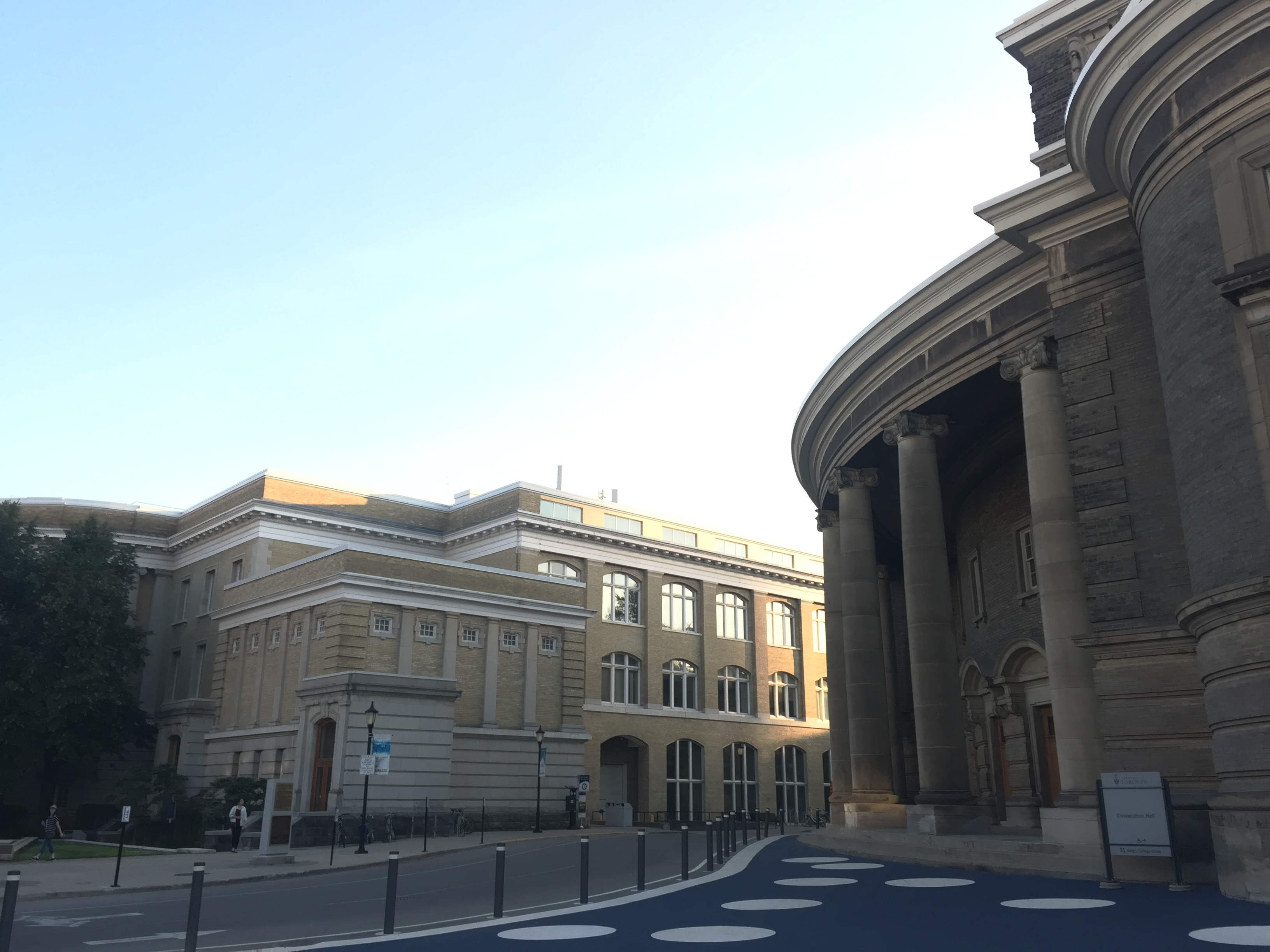 a photo of the pillars of convocation hall and the sanford fleming building beside the convocation hall with the road in between and blue skies above