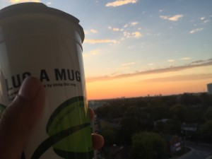 a photo of a white reusable travel mug against a sunrise backdrop, the sky is blue and orange and the travel mug is somewhat a silhouette, the travel mug has 'Lug a Mug' emblazoned across it with a picture of a green leaf