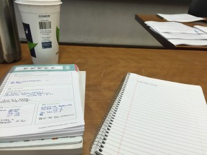 a photo of a notebook, a day planner and a coffee mug lying on a wooden table