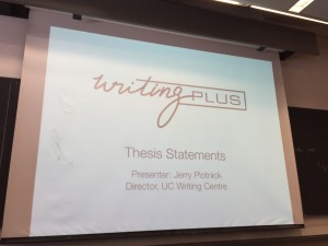 Photo of the title slide for Writing pLus class: Thesis Statement projecting on to a a white screen. The slide reads: Writing plus, Thesis Statements, Presenter Jerry Plotnick, Director, UC Writing Centre