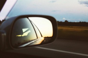 A picture of a car-side mirror during a sunset
