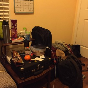 "ALT=""A photo of my nightstand and corner of the room cluttered with clothes."""