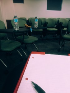 A picture of a clipboard with a piece of lined paper on top, in the foreground of an empty room filled with chairs