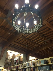 a photo of a medieval style wrought iron chandelier hanging from a vaulted ceiling with wood panels beside a mezzanine at a library