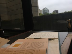 a photo of a an open text book laying on top of an open green binder on a dark table against a window that is looking out to the top of some buildings.