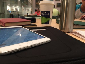a photo of a white tablet on top of a black case sitting on a light brown wooden table with two books in a stack behind it and a trabel mug and stainless steel water bottle placed to the right in front of a green binder