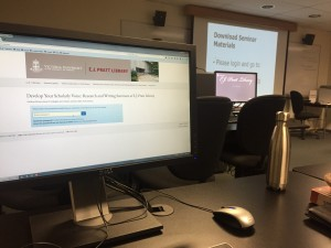 picture of a computer screen in a class room in front of a projector screen projecting slides from a seminar