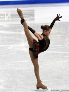A professional figure skater is shown doing an arabesque.