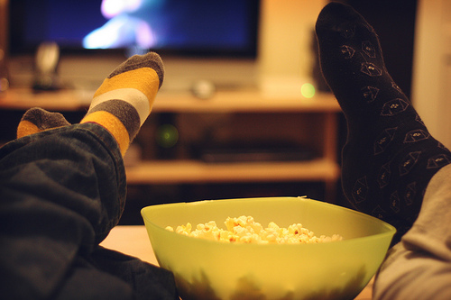 Feet propped up and popcorn bowl in front of TV