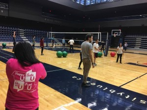 A game of balley ball is shown underway and a facilitator wearing a MoveU t-shirt.