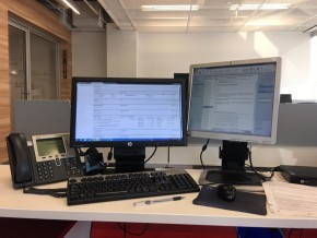 Two monitors,a phone on a desk
