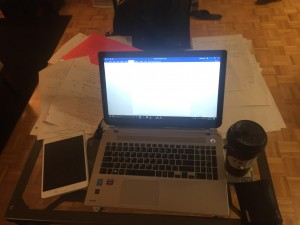 picture of laptop in the middle of an explosion of papers and a tablet beside it as well as black wallet and a brown coffee cup