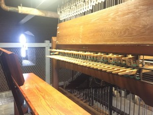 a photo of the carillon in the soldiers tower, essentially a wooden bench and the wooden keys of the organ like instrument with a window in the background
