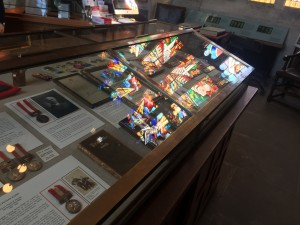 a photo of a glass cabinet that has war medals housed within it and with the reflection of stained glass on the cabinets surface