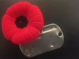 a photo of a red poppy pin on top of a metal military dog tag on a black surface