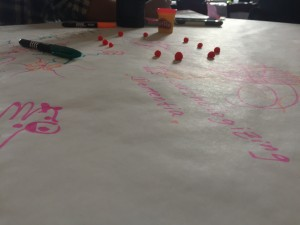 Picture of a table mat with notes written by people in pink regarding the conference material as well as balls of play-doh