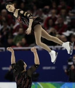 An awkward mid-flight photo of a figure skating pair.