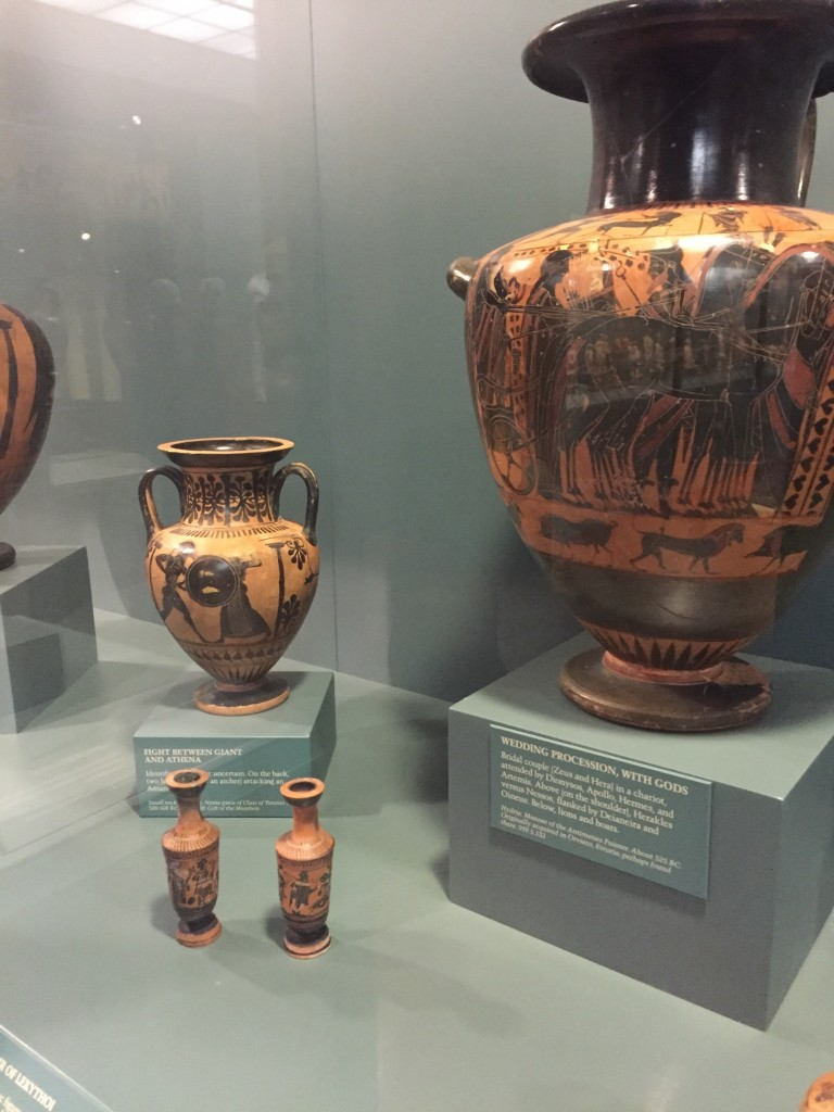 Display of Greek vases with artwork on them: one very large one and three smaller ones