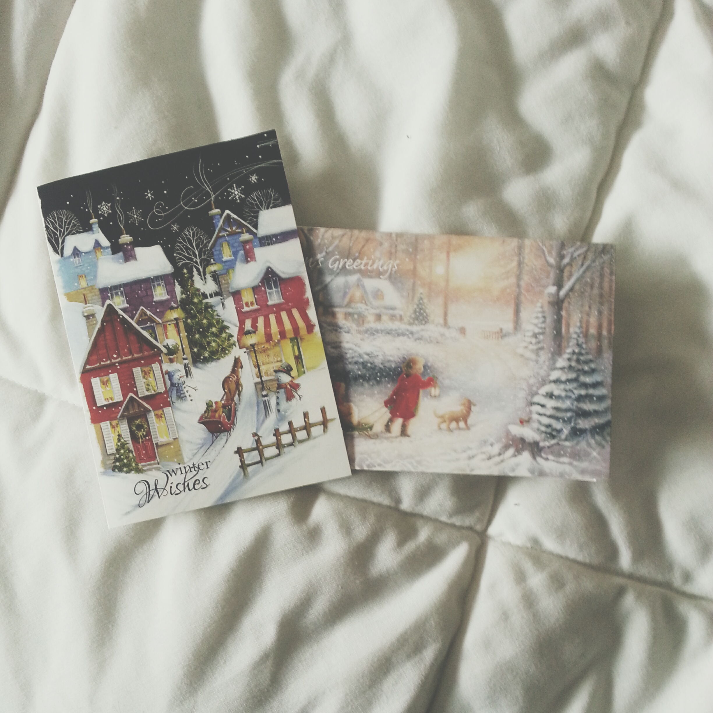 Two Christmas cards lying on a bed