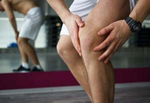 A man is seen gripping his knee as if in pain.