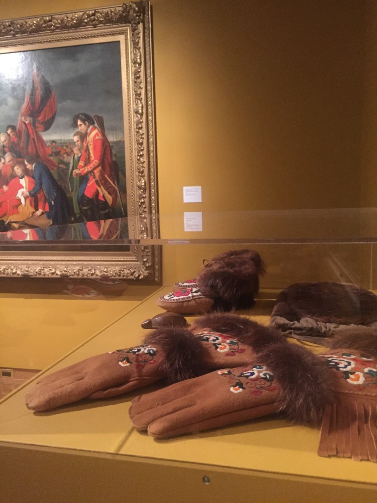 A display of gloves and moccasins in the foreground. In the background is another painting (not one of Monkman's)