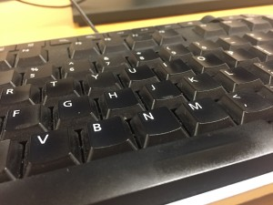 a photo of a black computer keyboard on a yellowish wooden table