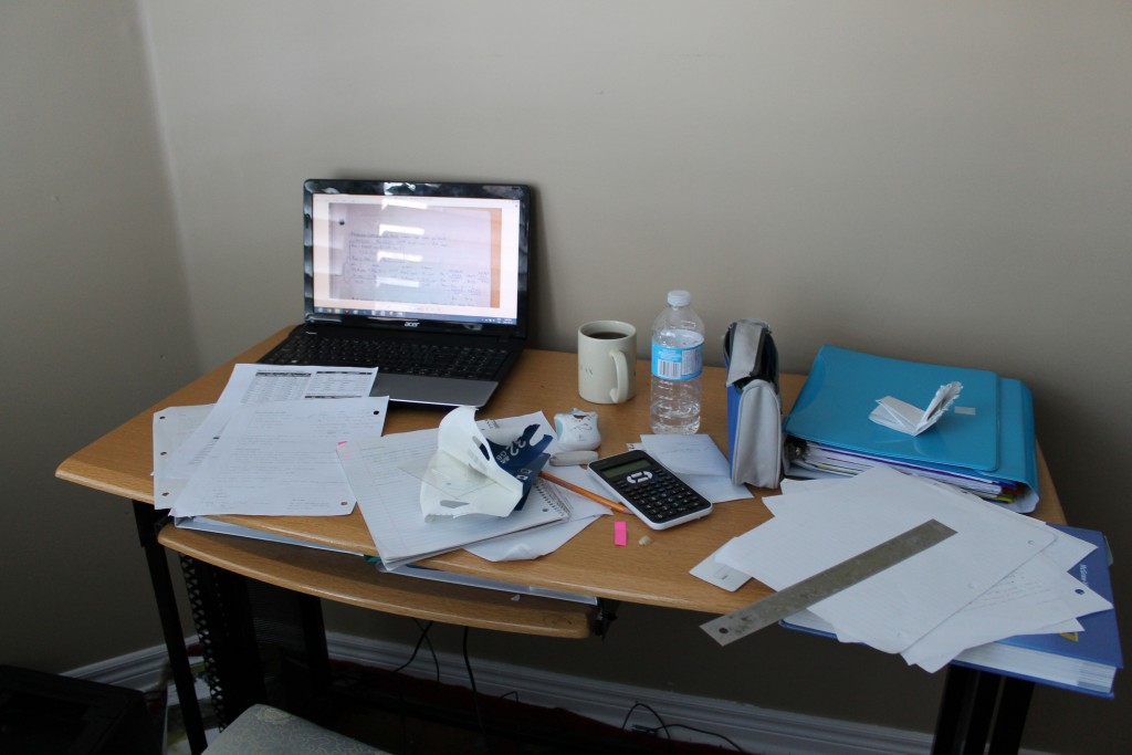 A picture of a messy cluttered desk with a laptop and notes everywhere