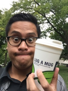 a photo of blogger Jasper holding a travel mug in a park making a strange face. Jaspe ris wearing a grey leather jacket and thick framed glasses. He is standing a in a park in front of many green trees.