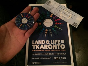 a photo of a hand holding a button hovering above the program for the 2017 hancock lecture and the box office ticket