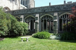 a photo of knox college quad, with a stone bench and a couple of bushes on a green lawn as the focal point