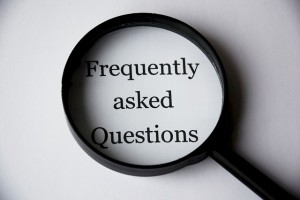 """A magnifying glass hovering over a paper that says """"Frequently Asked Questions"""
