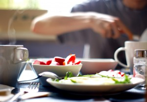 a stock photo of a breakfast table with red fruit in a white bowl, and eggs in a white plate, and a blurry image of a disembodied arm in the position of eating.