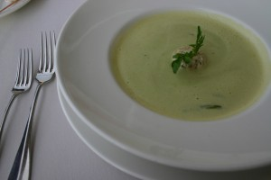 a photo of a green chile soup with a sprig of cilantro in the middle in a white wide rimmed bowl sitting on a white saucer, beside the soup are two different sized silver forks, and everything is on a table covered by a white table cloth
