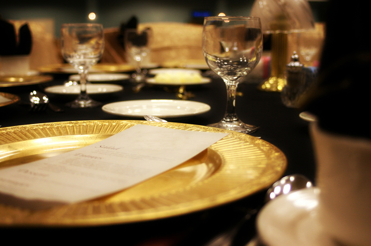 a photo of a dinner place setting with a gold plate and a white dinner roll plate and a wine glass on a table covered with a black table cloth