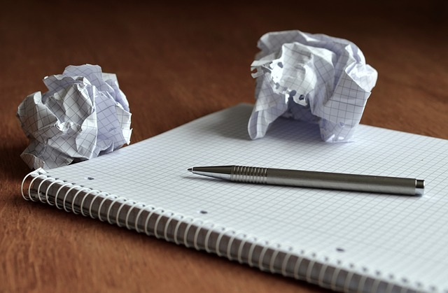 A picture of a notepad and pen with crumples balls of paper