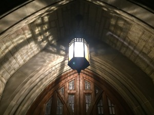 a photo of a lamp outside of the emmanuel college entrance, it is hanging from a grey stone arched ceiling and behind it is the upper portion of an wooden, arched doorway