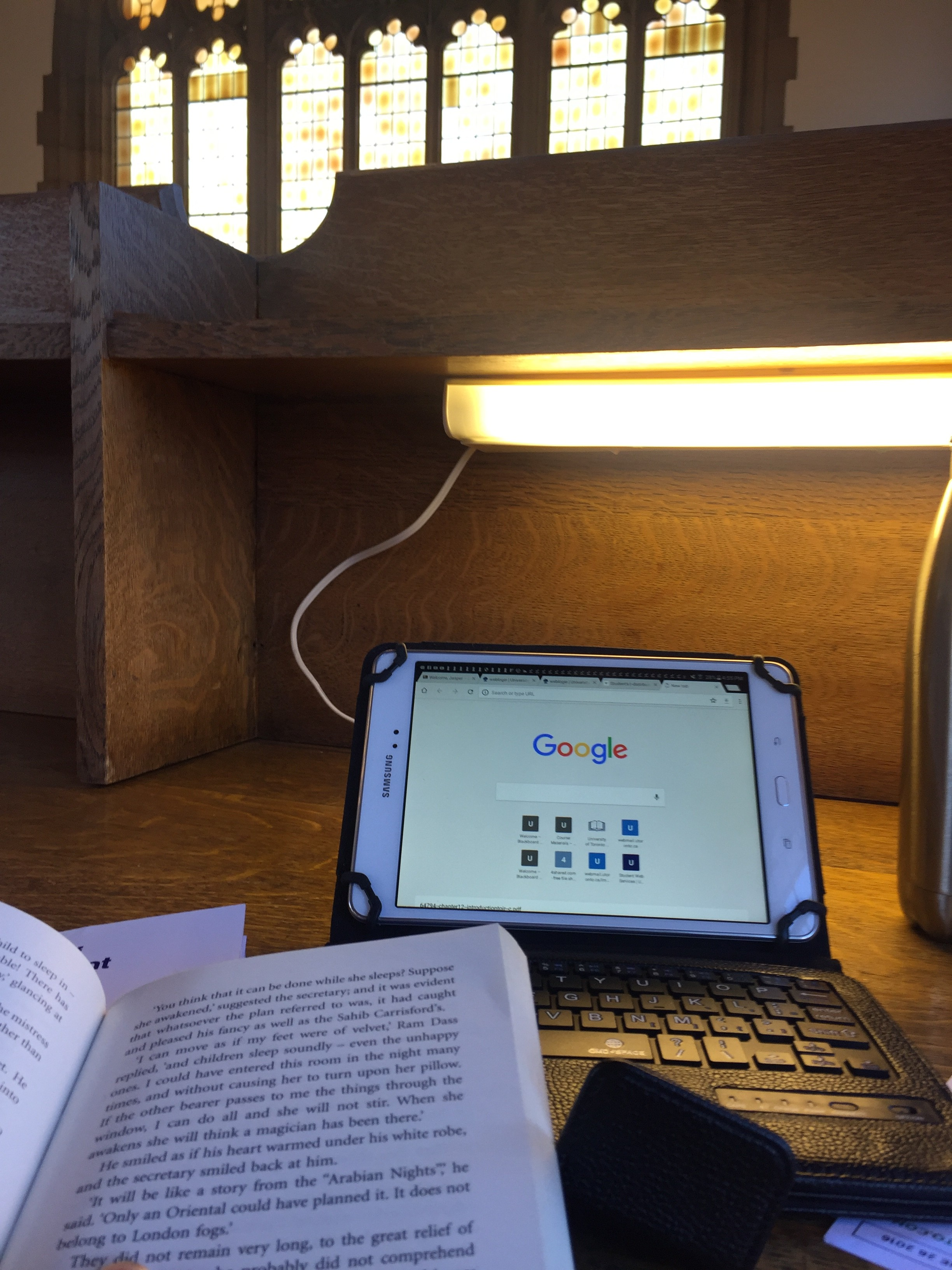 a photo of a work space on a light wooden desk where in the bottom left corner is a top portion of a novel, behind that there is a tablet on the Google homepage in a black case with a keyboard, and besie it is a part of a stainless steel water bottle all backdropped by a large gothic style yellow window