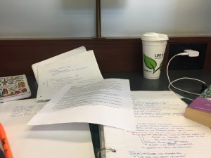 a picture of a work space on a dark wooden table, an open binder sits at the centre of the table with paper strewn across the table and a white and green travel mug sitting at the back of the table with charger wires peaking out from the right side of the picture and the bottom stem of a brass lamp at the centre back fo the table and an opaque glass divider that at the very back of the picture
