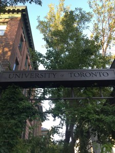 A photo of the University of Toronto gate with university of toronto etched on a steel barin front of a brick building and a tree.