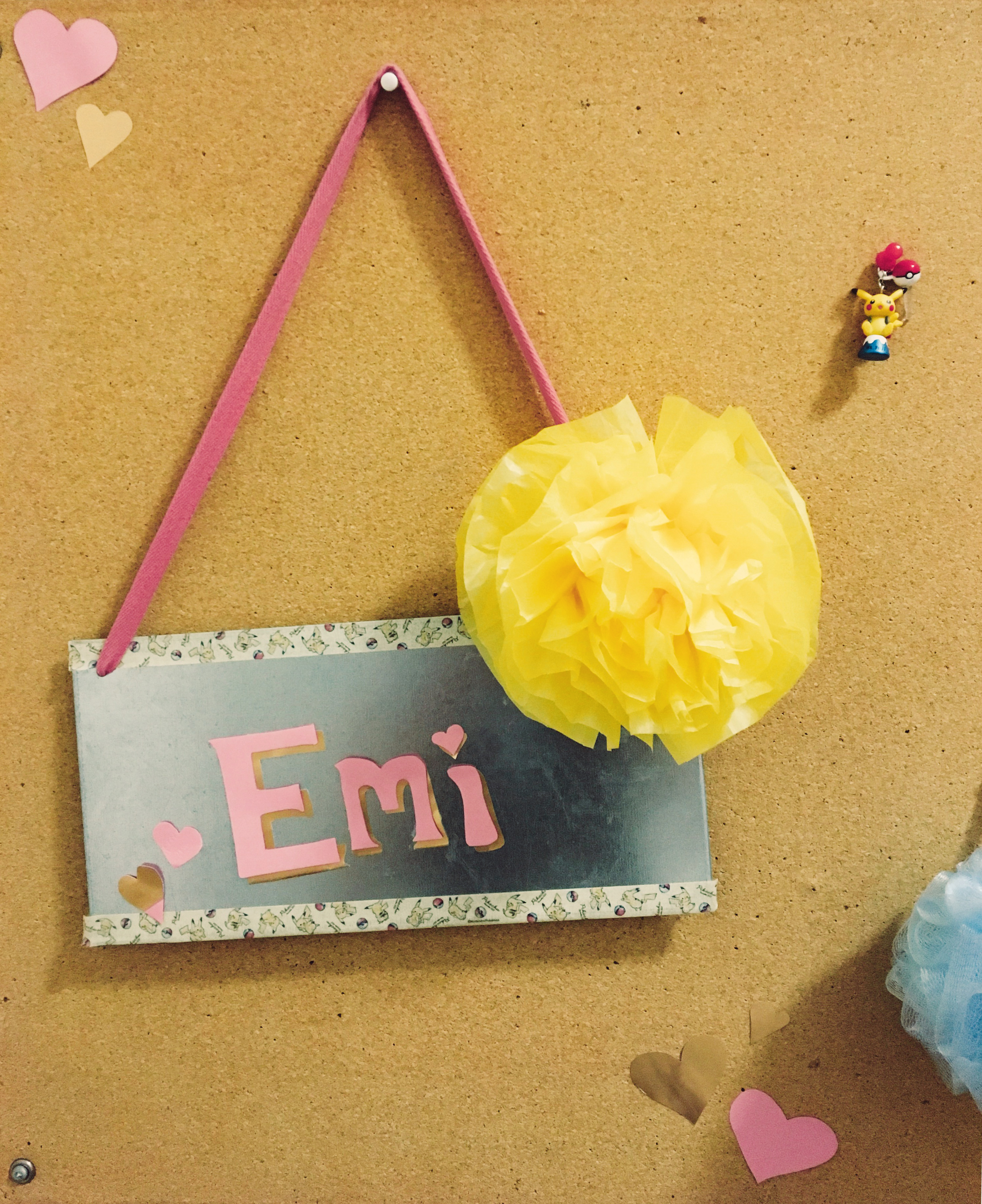"A picture of Emi's dorm bulletin board, with a sign that says ""Emi"" and a paper flower."
