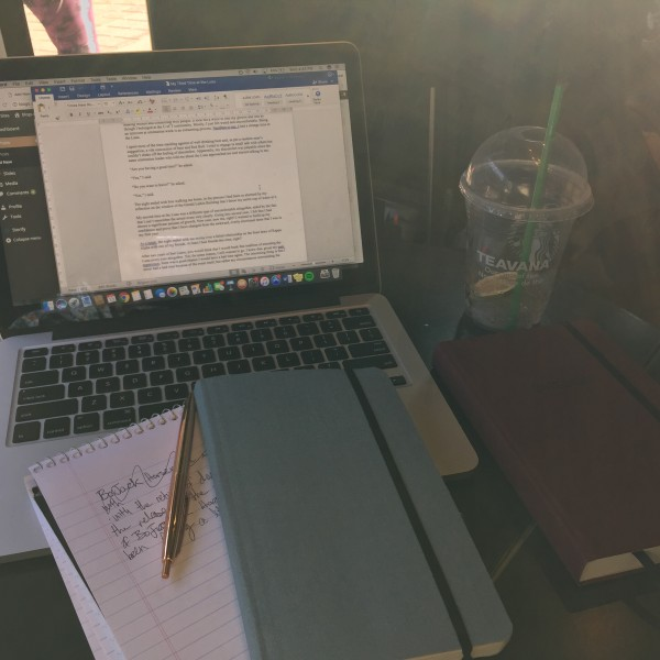 Picture of table with laptop, books, and a pen.