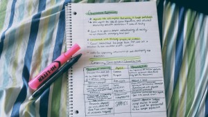 Pictured is an open notebook, face up, littered in bold black lettering and highlighted frequently in yellow and green. Beside said notebook are two writing utensils; a black pen and a pink highlighter.