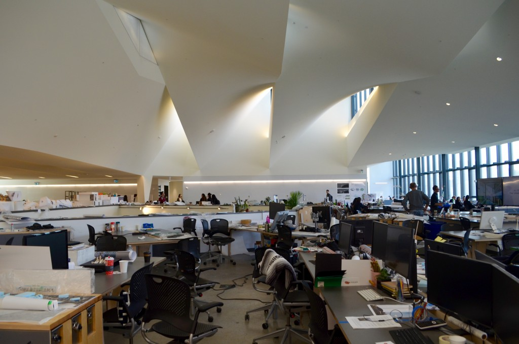 large, open, graduate studies studio space with desks everywhere and white ceilings with openings