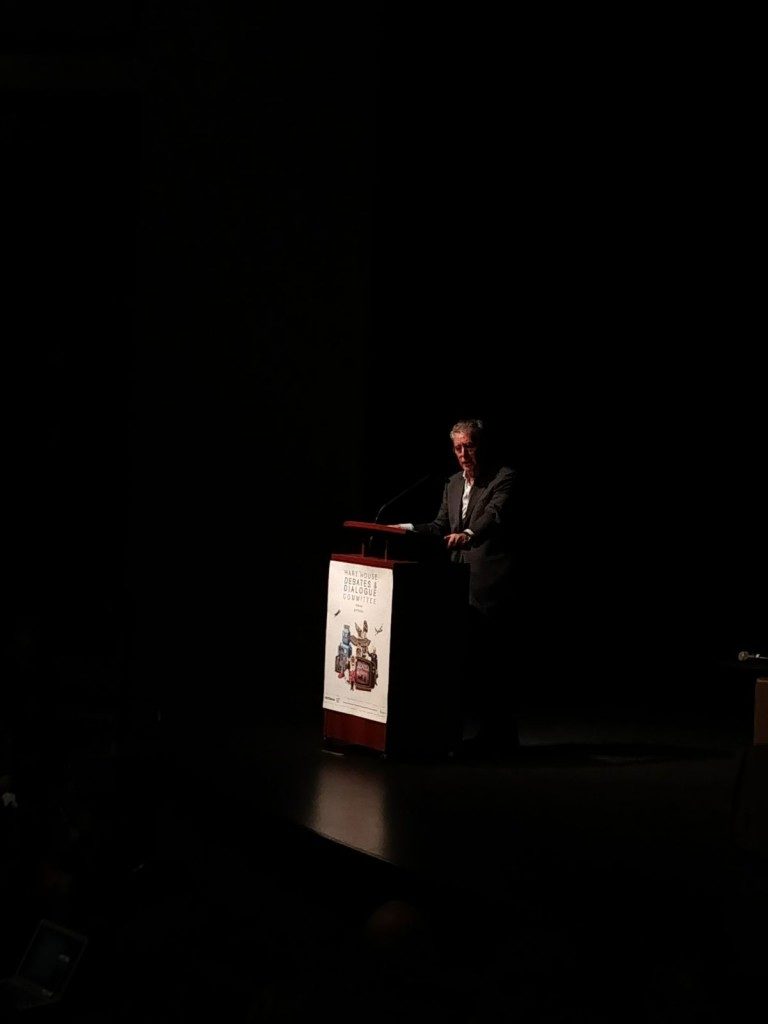 Mr. Dennis Edney on stage, at the podium, addressing his audience at the event