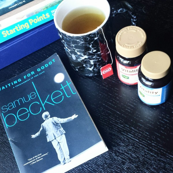 """An image of a mug of tea, two containers of multivitamins and the playbook """"Waiting for Godot"""" assorted on a black coffee table."""