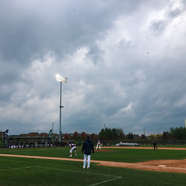 A baseball game takes place under a cloudy sky.